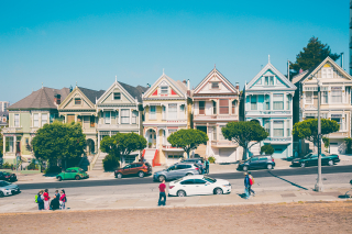 People and cars on a hill with bright colorful houses in San Francisco